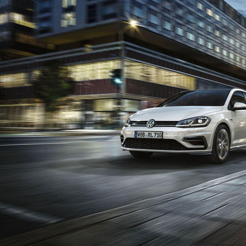Volkswagen Golf visto por delante acelerando por una calle de noche
