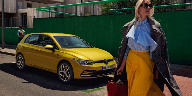 Mujer joven caminando delante de un Golf 8 amarillo aparcado en la calle