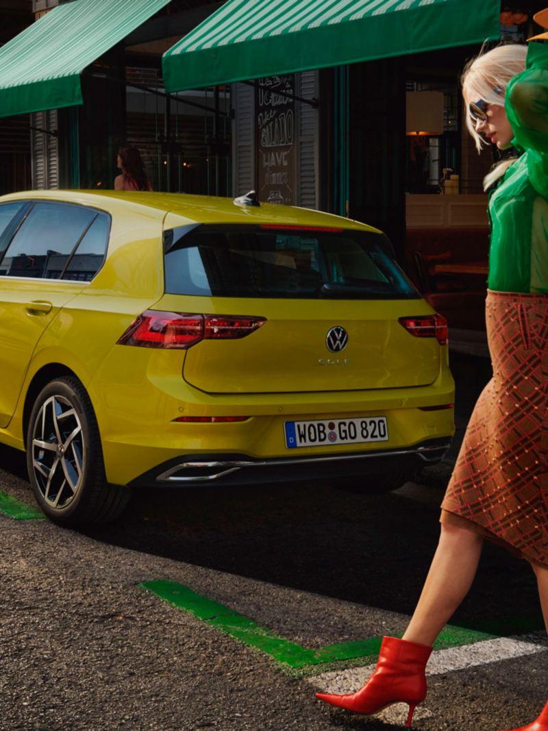 Vista trasera de Golf 8 amarillo aparcado en la calle con una mujer poniéndose un abrigo delante