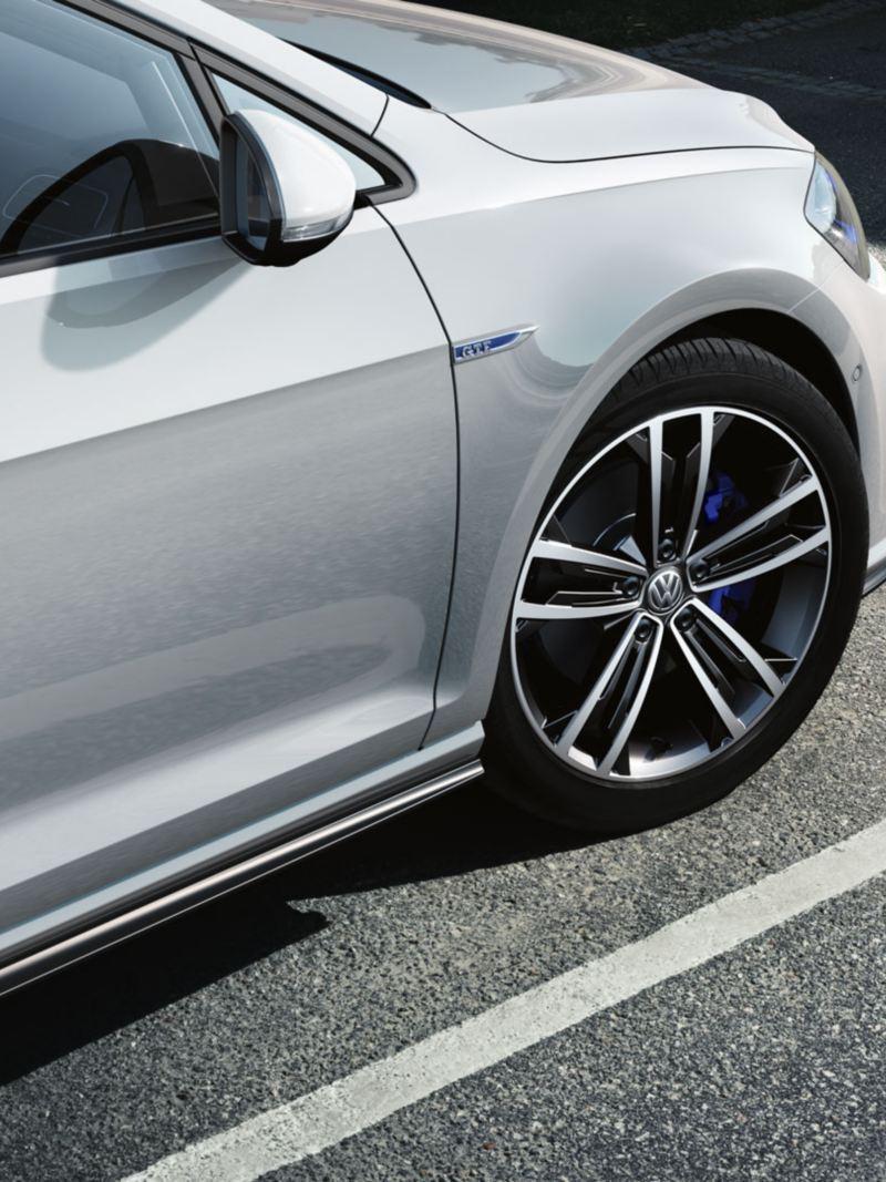 Vista lateral de un Golf GTE blanco aparcado en una plaza de aparcamiento