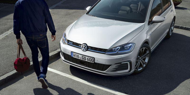 Hombre con una bolsa hacia un Golf GTE blanco en una plaza de aparcamiento en la calle