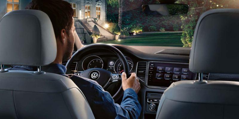 Hombre con las manos en el volante de un Golf Sportsvan visto desde los asientos traseros