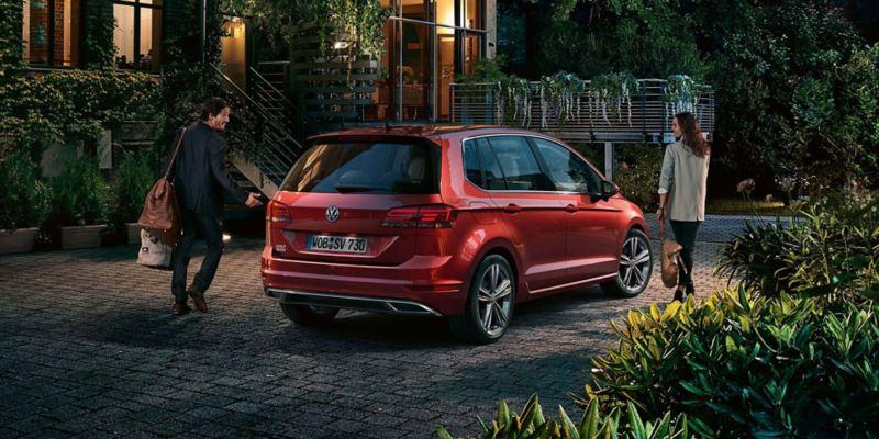 Vision trasera de un Golf Sportsvan rojo aparcado tras una casa por la noche