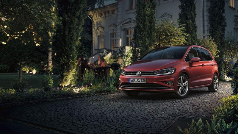 Volkswagen Golf Sportsvan rojo cranberry aparcado en un jardín de noche mientras una pareja sale de casa