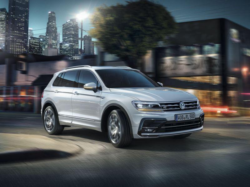 Volkswagen Tiguan blanco con R-Line circulando por la ciudad de noche