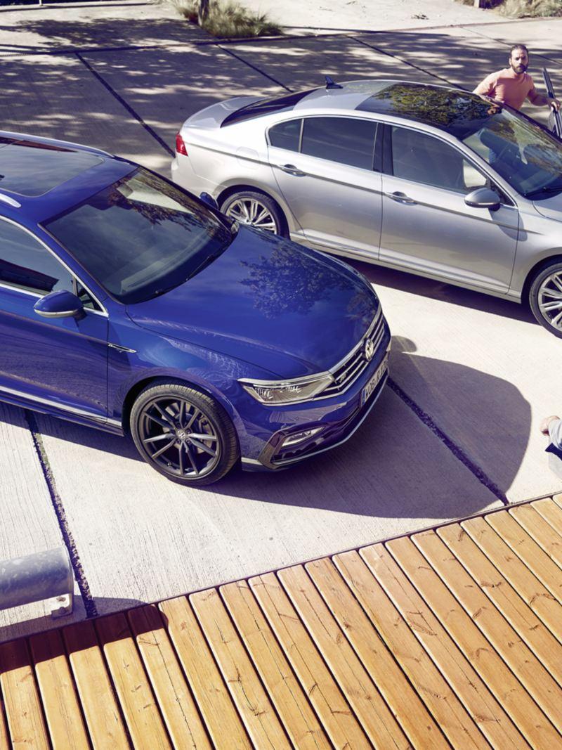 Passat gris y Passat Variant azul aparcados con dos hombres jóvenes