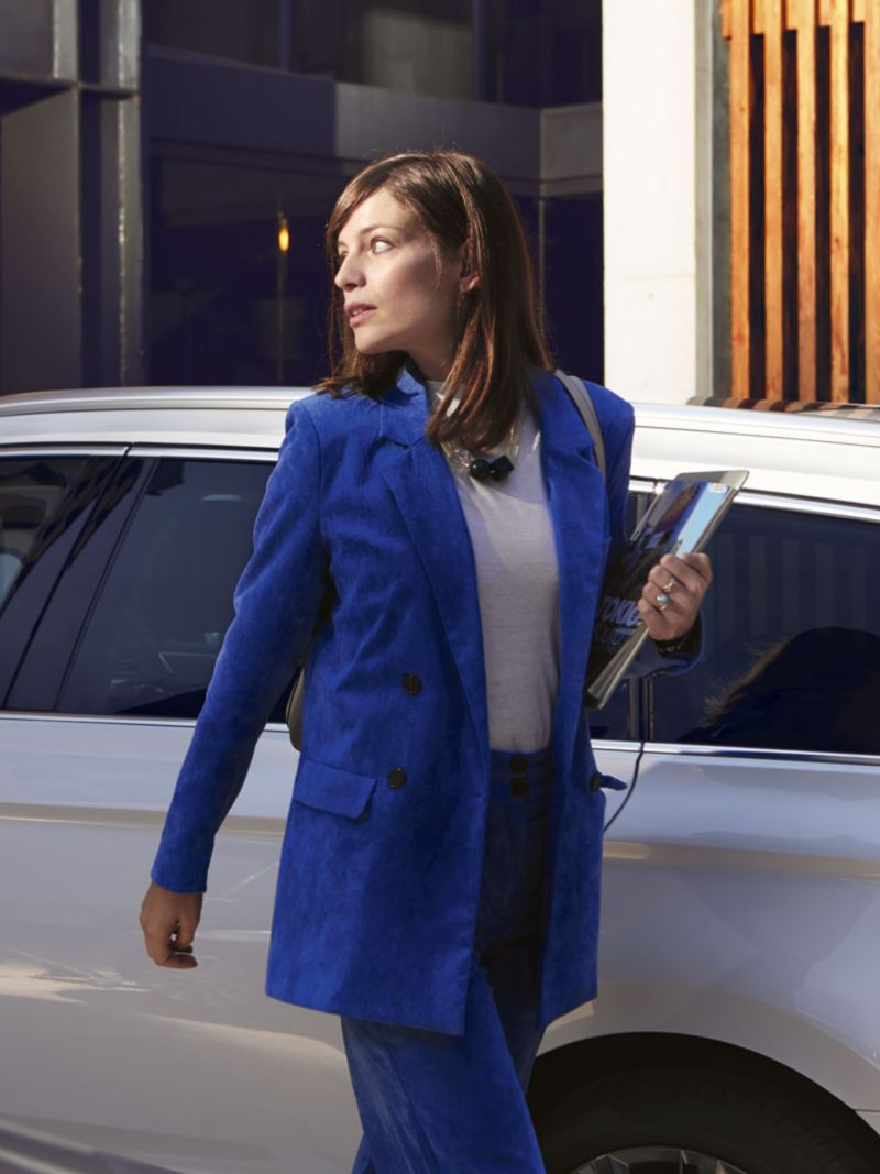 Mujer joven caminando delante de un Volkswagen Passat GTE Variant