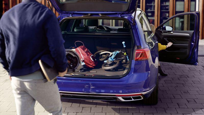 Hombre delante del maletero abierto de un Volkswagen Passat Variant cargado con una mochila y una bicicleta de niño