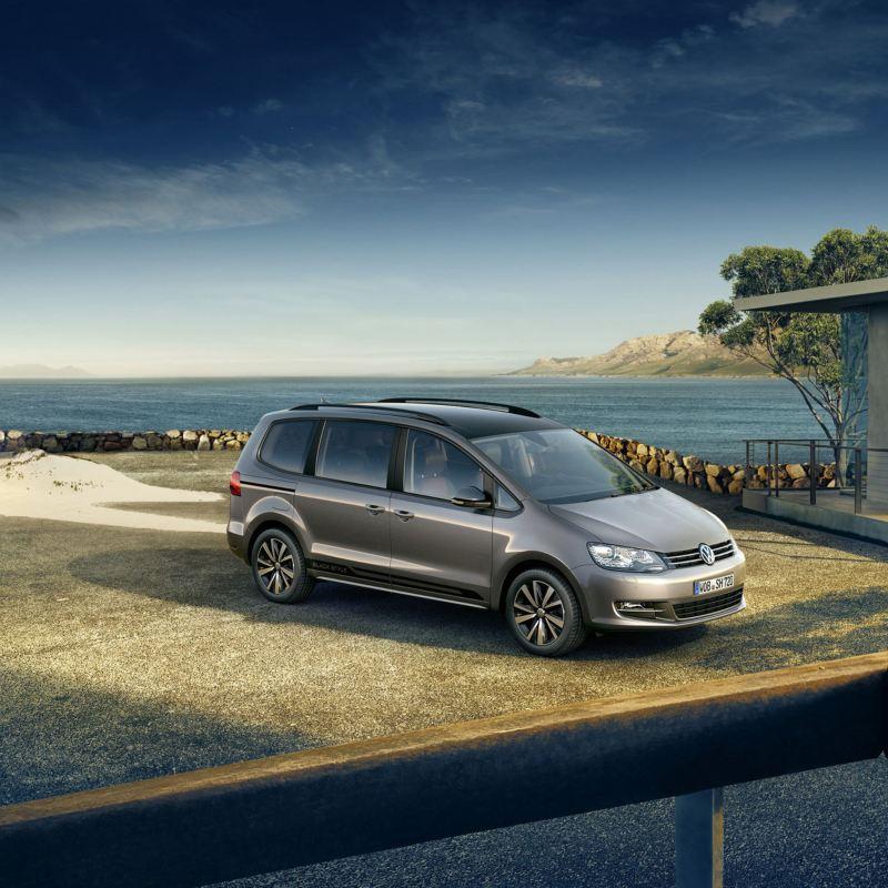 Volkswagen Sharan color plata, coche familiar aparcado delante de una casa junto al mar