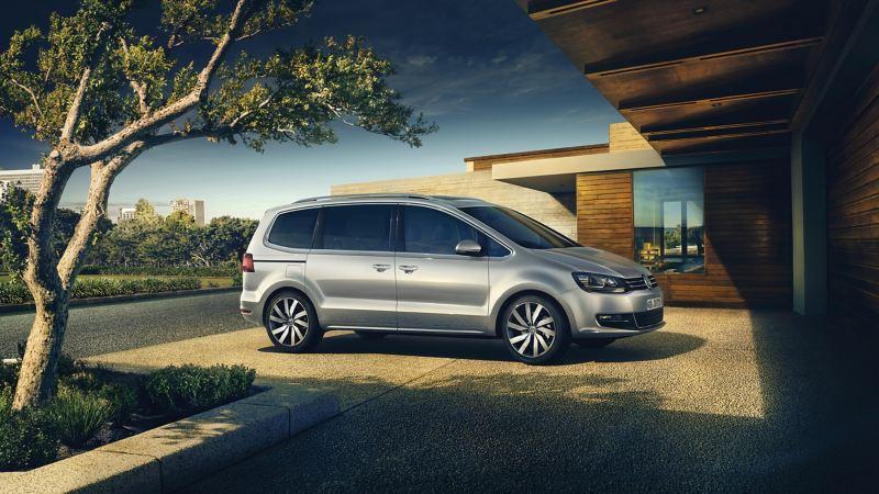 Volkswagen Sharan color plata, coche familiar aparcado delante de una casa