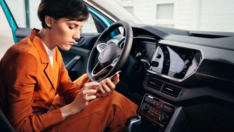 Chica sentada en un T-Cross azul turquesa con la puerta abierta usando su teléfono móvil