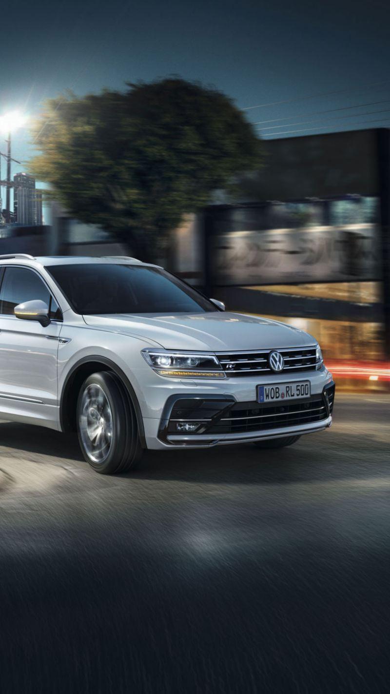 Volkswagen Tiguan blanco circulando por la ciudad de noche