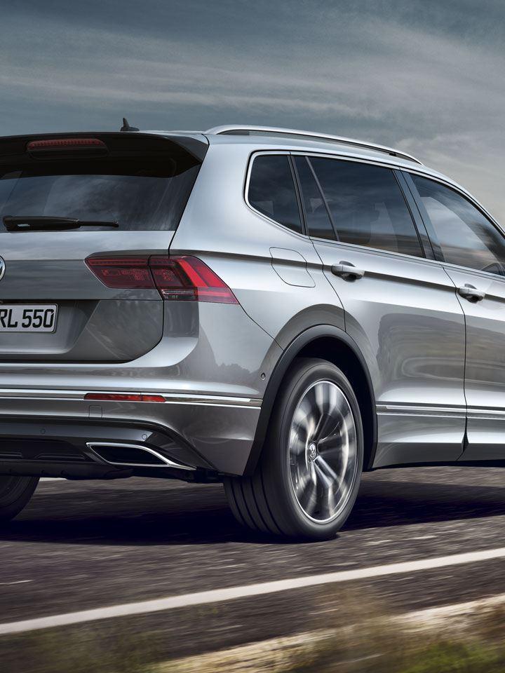 Volkswagen Tiguan Allspace gris circulando por una carretera junto al mar