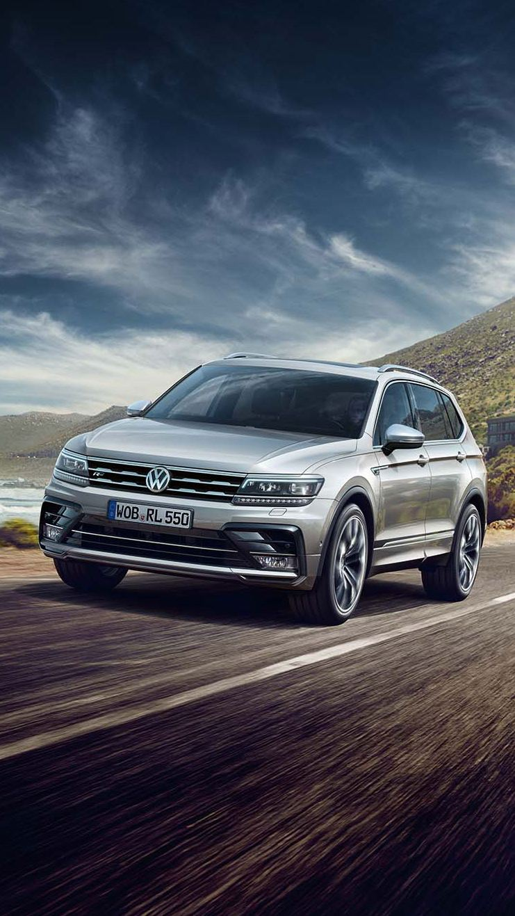Volkswagen Tiguan Allspace gris circulando por una carretera junto al mar y delante de las montañas