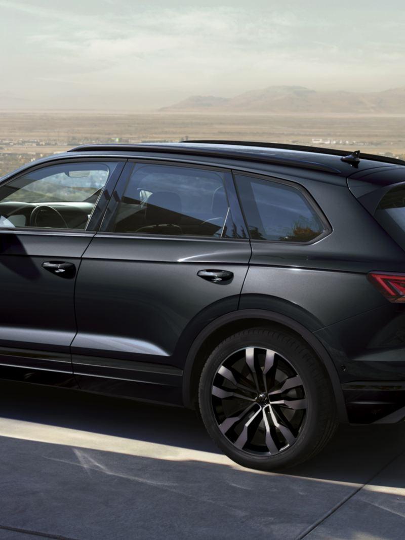 Volkswagen Touareg negro aparcado frente a una casa con vista a una ciudad al fondo
