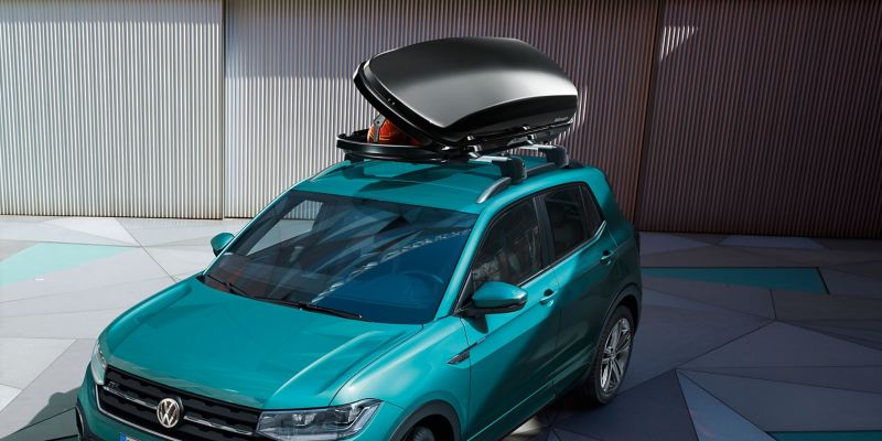A turquoise VW T-Roc with an opened VW accessories roof box on his roof