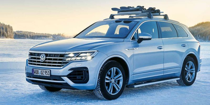 A silver VW car with a ski and snowboard in a snowy landscape