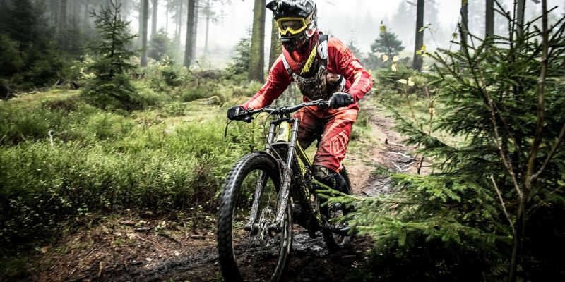 Christian Junker rides his mountain bike along a muddy track in a forest