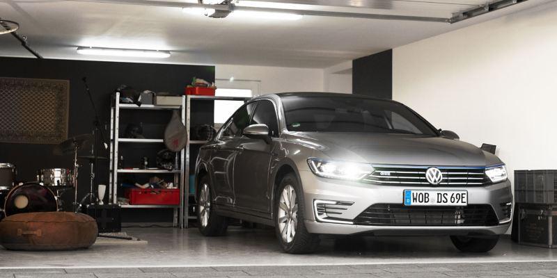 Ein neuer silberner Passat GTE mit leuchtenden Scheinwerfern steht in der Garage