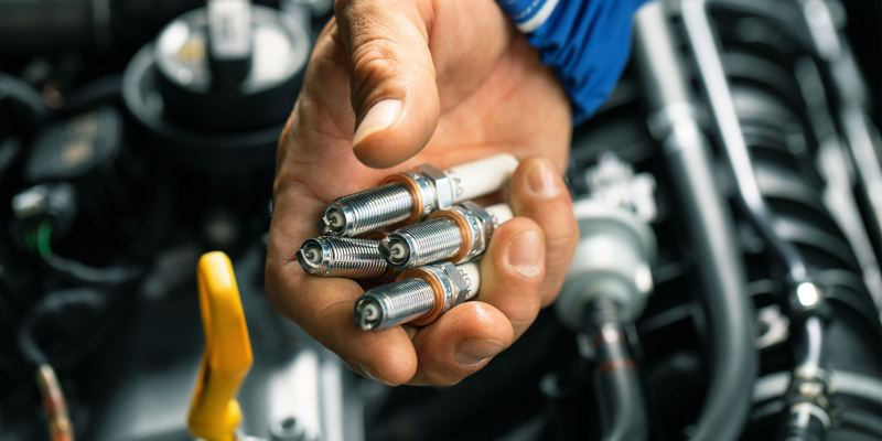 VW service employee holds four Volkswagen Genuine Spark Plugs in his hand