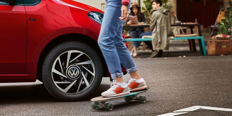 Une femme en skateboard passe devant une Volkswagen Up!