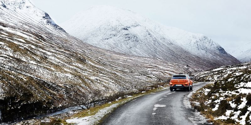 An orange VW vehicle drives on a wintry road in the mountains