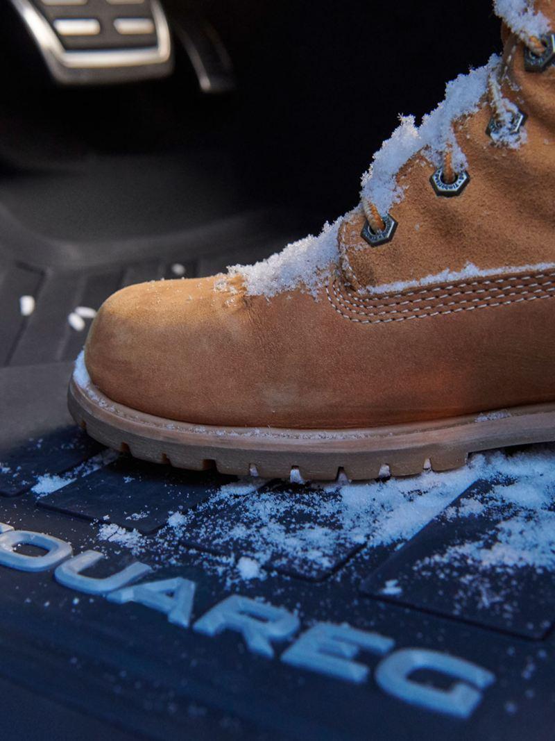 Giày boot leo núi trong mùa đông nằm trên thảm lót sàn - phụ kiện Volkswagen của chiếc VW Touareg