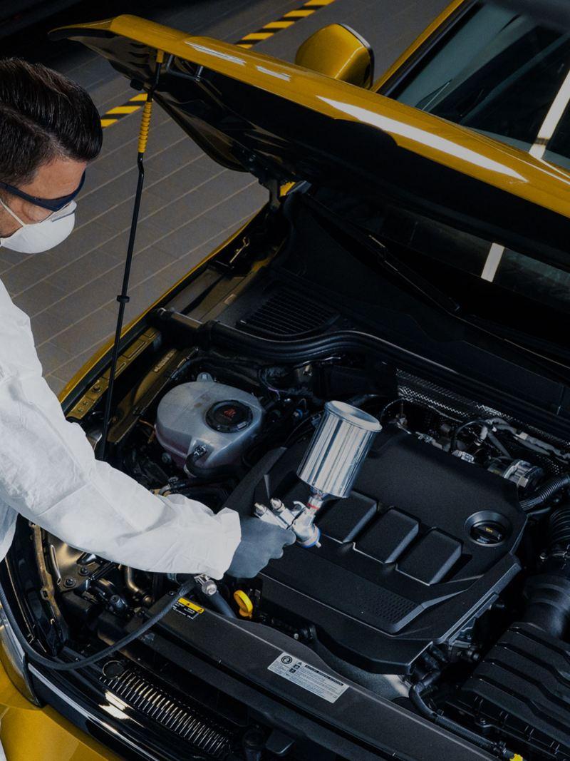 Un addetto di Volkswagen Service sta lavorando su un'auto a cofano aperto.