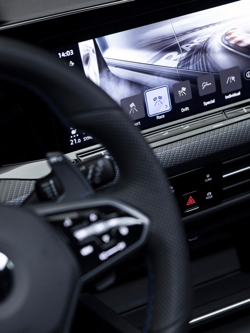 A close-up view of the steering wheel inside the all-new 2022 Golf R. We see the Digital Cockpit Touchscreen behind displaying one of various driving modes.