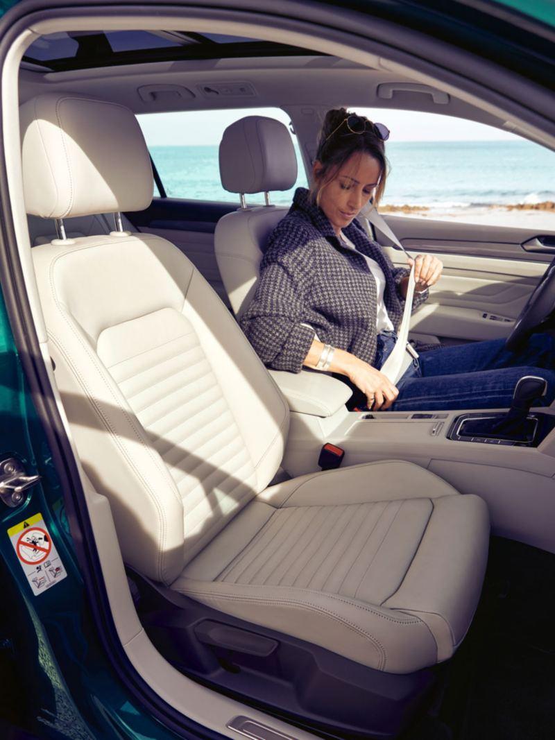 Mujer joven poniéndose el cinturón de seguridad en el puesto del conductor del Passat Alltrack