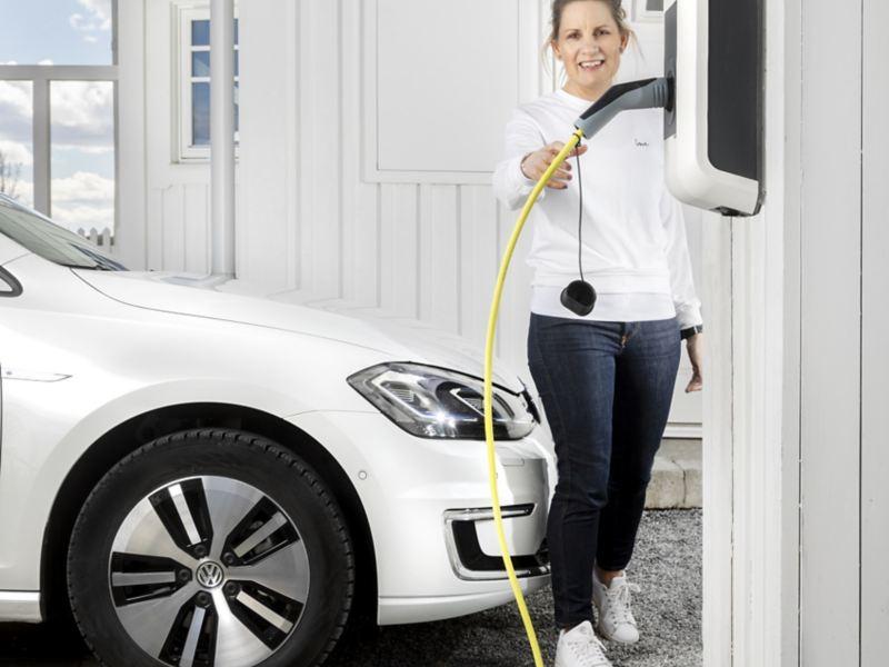 Volkswagen e-Golf, kvinna sträcker sig efter laddningskabeln