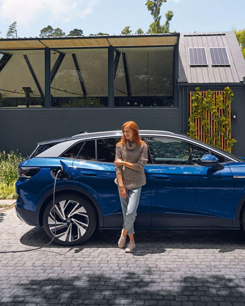Der vollelektrische ID.4 von Volkswagen fährt zügig auf einer Landstraße vor blauem Himmel.