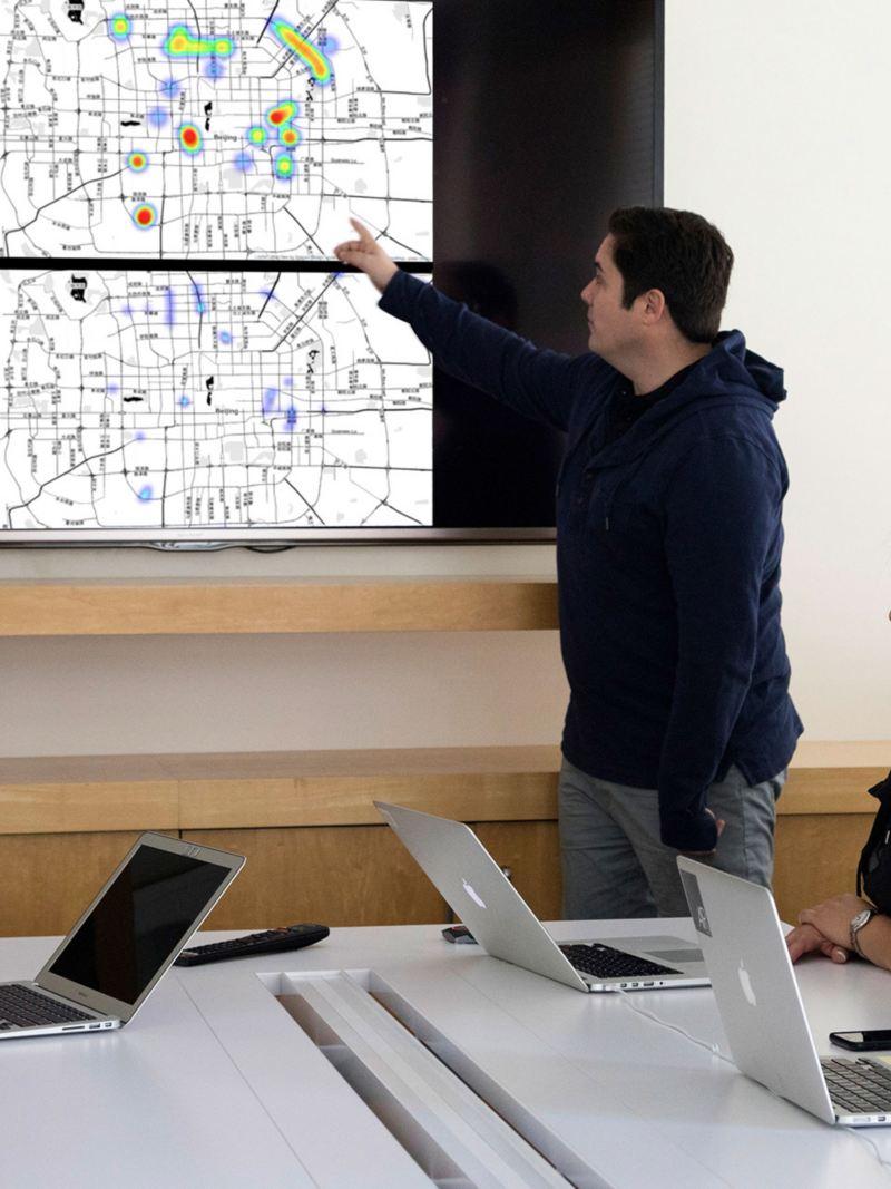 Ein Mann erläutert vor einer Gruppe Zuhörer eine Grafik