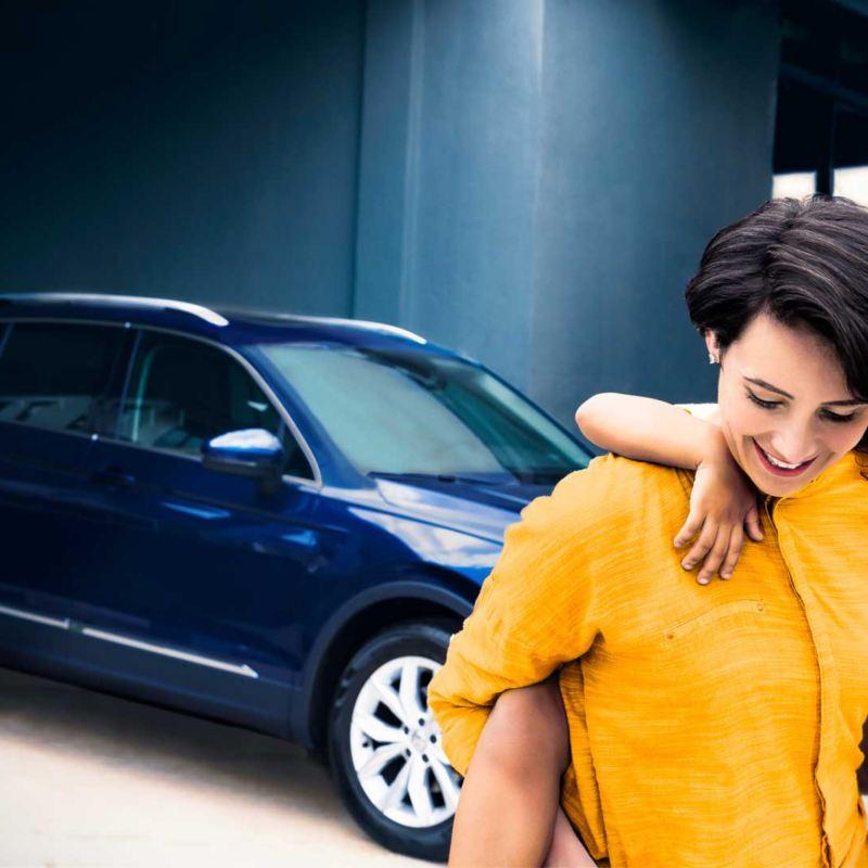 Frau mit Kind vor einem VW Tiguan