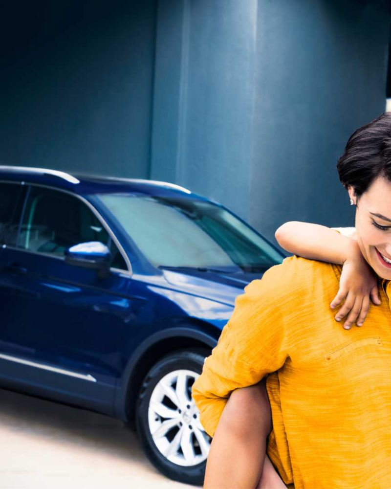 Une femme avec un enfant devant un VW Tiguan