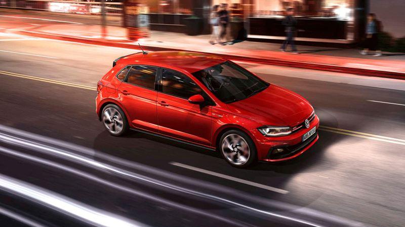 Volkswagen Polo GTI rojo avanzando en la calle con reflejos de luz