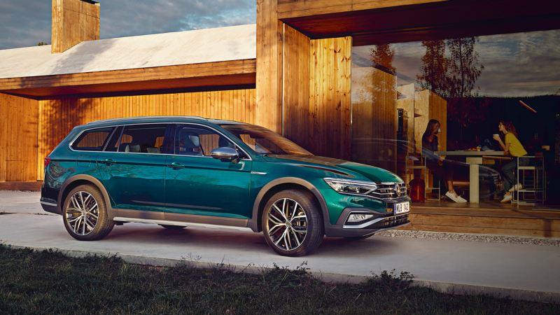 Volkswagen Passat Alltrack aparcado delante de una casa, se ven dos mujeres tomando café en el interior