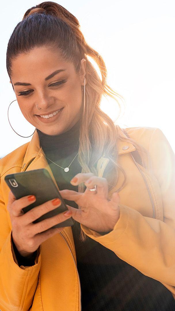 Eine junge Dame schaut lächelnd auf ihr Smartphone