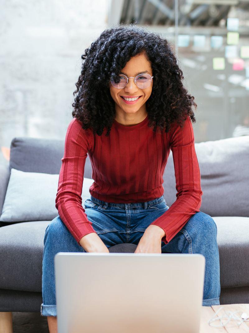 Eine Frau sitzt auf dem Sofa vor ihrem Laptop