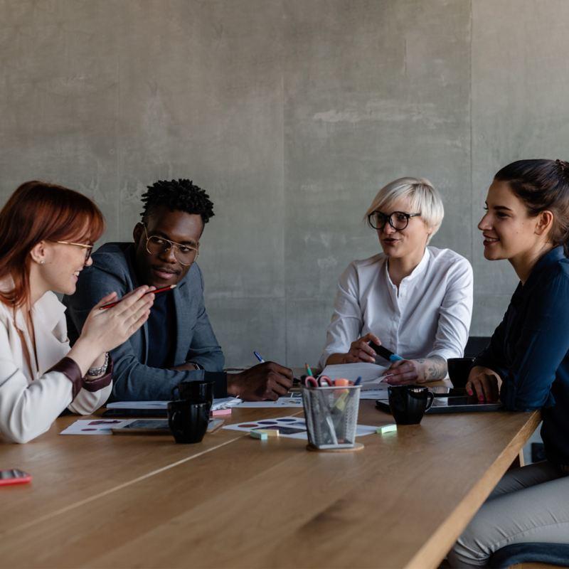 Drei Frauen und ein Mann unterhalten sich an einem Tisch
