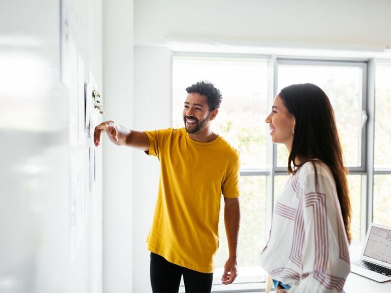 Eine Frau und ein Mann arbeiten an einem Whiteboard