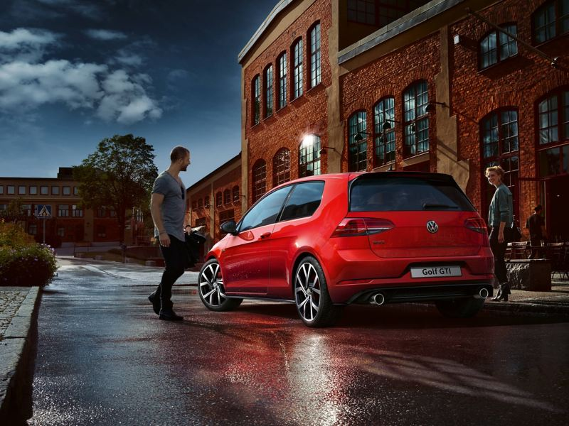 Rear shot of red Vokswagen Golf GTI outside a warehouse at dusk, a man and woman getting in.