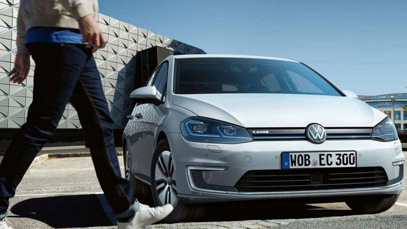 Mann geht zu seinem VW e-Golf mit bestehender LongLife Mobilitätsgarantie