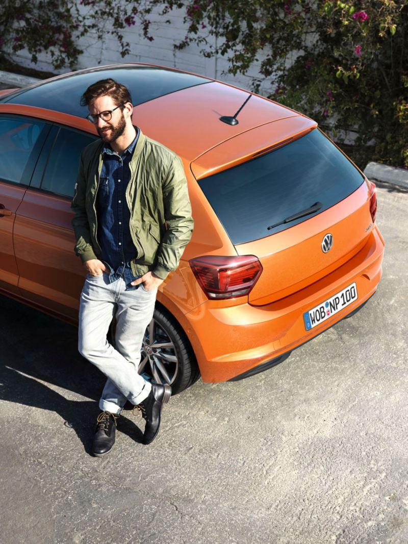 Chico apoyado en la parte trasera de un Volkswagen Polo naranja