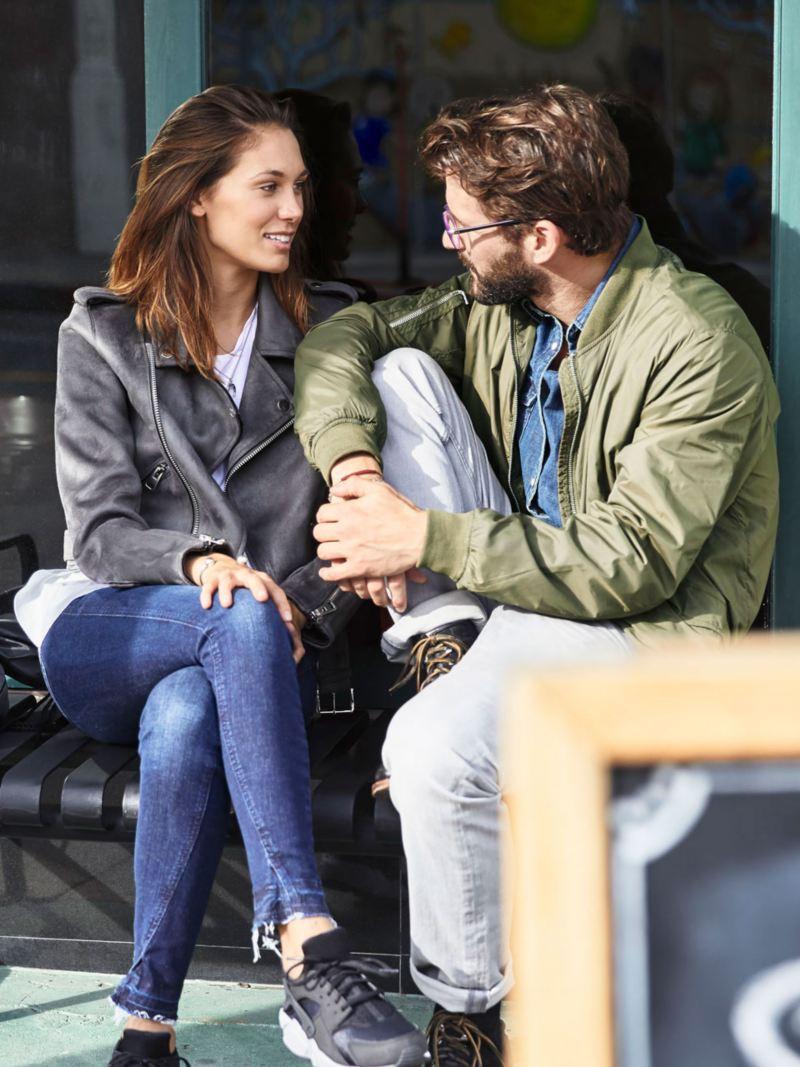 Pareja sentados en un banco de la calle mientras hablan