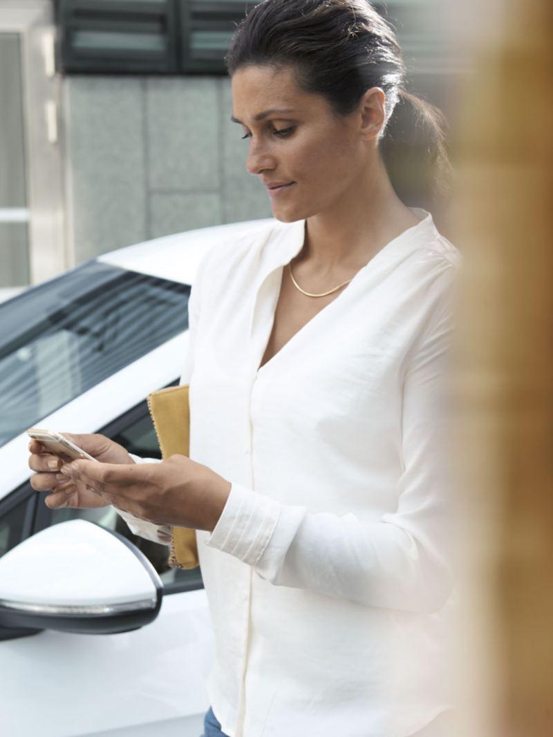 Mujer mirando su teléfono móvil mientras camina junto a un e-Golf blanco aparcado