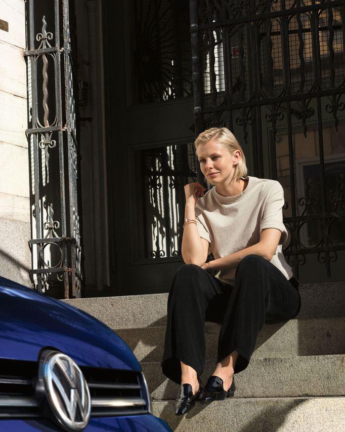 Mujer joven sentada en una escalera, en primer plano el frontal de un Volkswagen azul