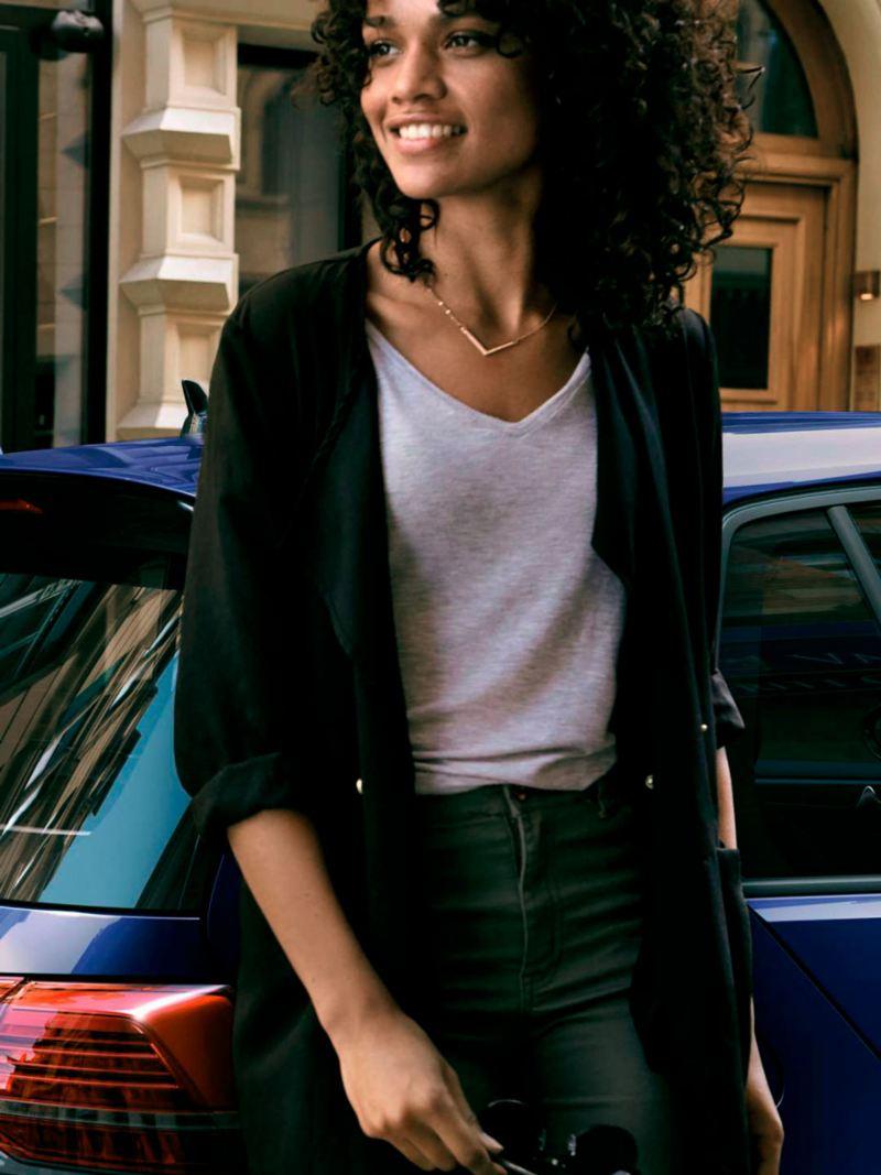 Mujer joven en la ciudad con un Volkswagen Golf azul detrás