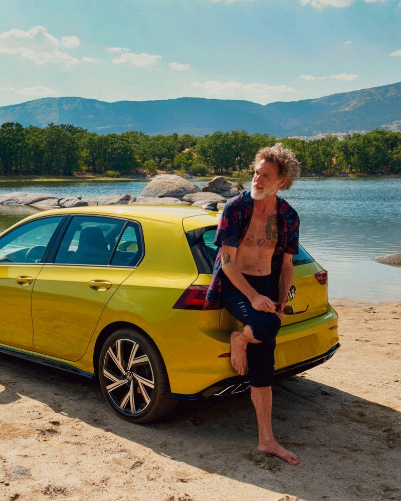 Hombre apoyado en la parte trasera de un Golf 8 amarillo aparcado frente a un lago