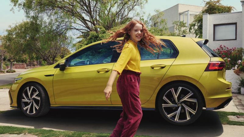 Niña pelirroja sonriendo delante de un Volkswagen Golf 8 amarillo lima aparcado delante de una casa